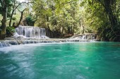The waterfall and small cool pond with turquoise water. Fantastically beautiful nature with clear water forest and wild jungle. Concept of ecological tourism