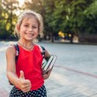 Happy pupil girl wearing backpack and holding book...