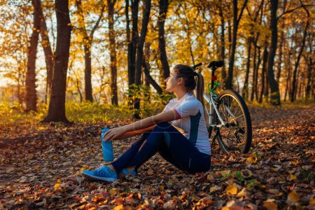 Photo for Riding bicycle in autumn forest. Young woman having rest after workout on bike. Healthy active lifestyle - Royalty Free Image