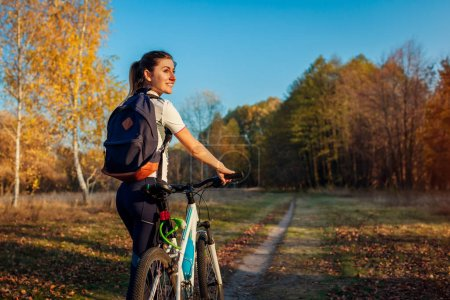 Photo for Bicycle ride in autumn park. Young woman traveler resting after riding a bike in suburbs. Healthy training outdoors - Royalty Free Image