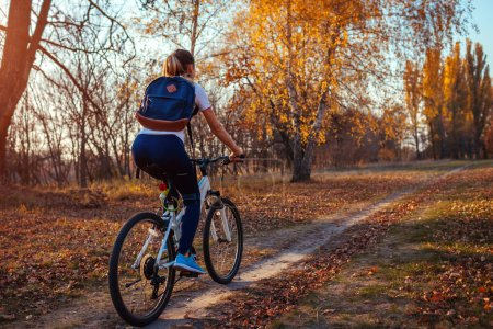 Photo for Bicycle ride workout in autumn park. Young woman biker with backpack riding a bike in fall forest. Healthy training outdoors - Royalty Free Image