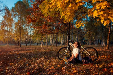 Photo for Riding bicycle in autumn forest. Young woman biker relaxing after exercising on bike under yellow trees outdoors. Healthy lifestyle - Royalty Free Image