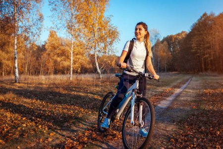 Photo for Riding bicycle in autumn forest. Young woman having rest after workout on bike enjoying nature. Healthy active lifestyle. Sport - Royalty Free Image