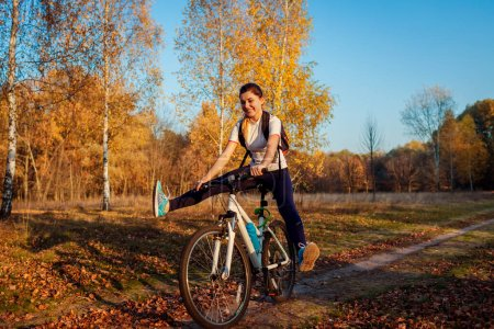 Photo for Bicycle ride workout in autumn park. Young woman biker riding a bike in fall forest having fun raising legs. Healthy training outdoors - Royalty Free Image