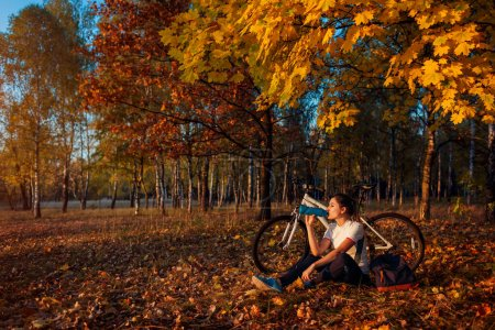 Photo for Young woman drinks water after workout on bike. Healthy lifestyle. Riding bicycle in autumn forest. Healthy active lifestyle - Royalty Free Image