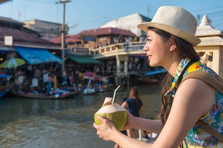Asian female drinks the coconut drink and enjoy the pleasant view of the floating market.