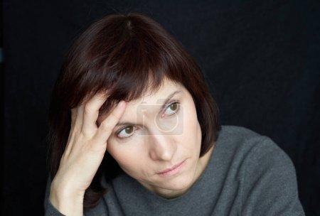 Madura, mujer de mediana edad mira con ansiedad lejos, tocando la frente y el cabello con la mano