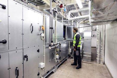 Photo pour Travailleur dans la salle des appareillages électriques de l'usine CNC - image libre de droit