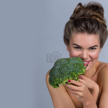 Portrait of a beautiful woman with perfect skin holding broccoli, gray background