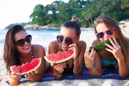 Foto de Felices amigas sonrientes comiendo sandía en la playa - Imagen libre de derechos