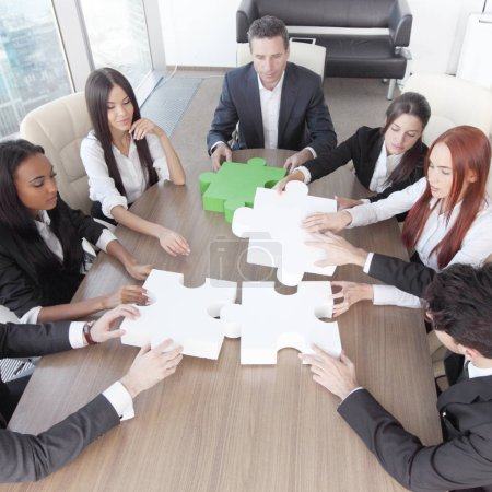 Photo for Group of business people assembling jigsaw puzzle and represent team support and help concept in office - Royalty Free Image