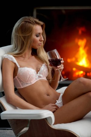 Sexy Frau in Dessous mit Wein am Kamin