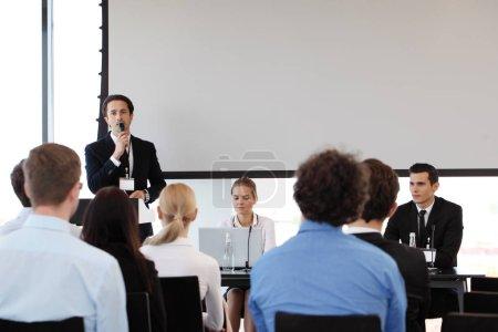 Photo pour Orateur à la Conférence d'affaires près d'écran blanc et le public - image libre de droit