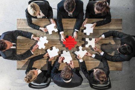 Foto de Gente de negocios y rompecabezas en la mesa de madera, concepto de trabajo en equipo - Imagen libre de derechos