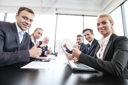 Photo pour Groupe composé de personnes en réunion de travail avec des documents et des ordinateurs montrant les pouces vers le haut d'affaires - image libre de droit
