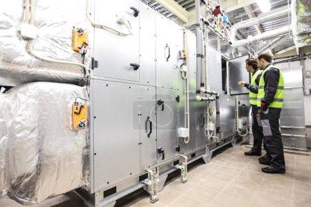 Photo pour Travailleurs dans la salle des appareillages électriques de l'usine CNC - image libre de droit