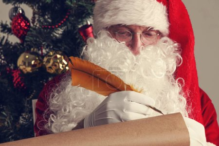 Photo for Santa Claus sitting at home and writing on old paper roll to do list with quill pen and ink - Royalty Free Image
