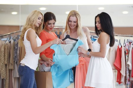 Photo for Young happy women choosing dress on sale in shopping mall - Royalty Free Image