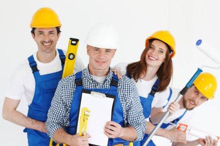 Photo pour Équipe de travailleurs souriants heureux avec des outils et des contrats - image libre de droit