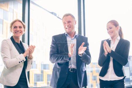 Photo pour Gens d'affaires du groupe frappant et souriant dans la position du Bureau autour de table de réunion - image libre de droit