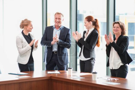 Photo for Business people group clapping and smiling in office standing around meeting table - Royalty Free Image