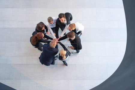 Photo for High angle view of a team of united businesspeople standing with their hands together in a huddle in the - Royalty Free Image