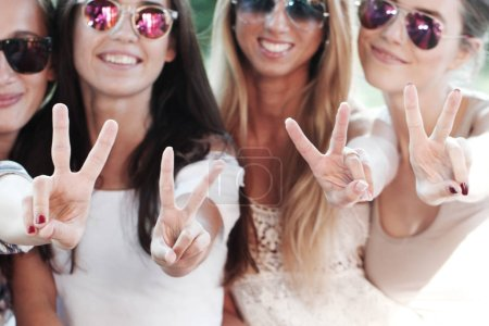 Photo for Happy smiling girlfriends showing a v hand sign - Royalty Free Image