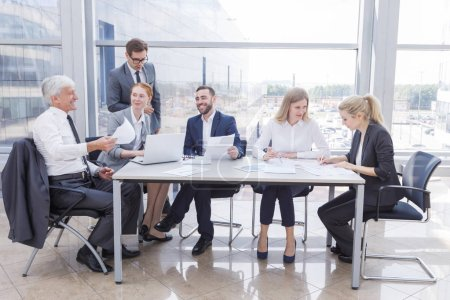 Photo for Business team sitting by the table with laptop and documents in office - Royalty Free Image