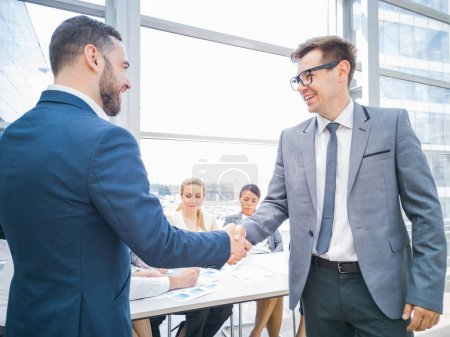 Photo for Handshake of business partners after discussion of the financial reports, their team on background - Royalty Free Image