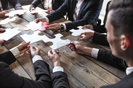 Photo for Business people and puzzle on wooden table, teamwork concept - Royalty Free Image