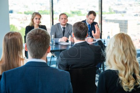 Photo for Audience of business people sitting at training room and talking, speakers sitting at the table with documents, microphones and water - Royalty Free Image