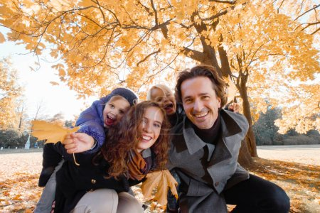 Photo for Happy smiling family of parents and children having fun hugging in autumn park - Royalty Free Image
