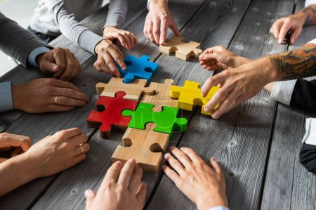Photo for Business people team sitting around meeting table and assembling color jigsaw puzzle pieces unity cooperation ideas concept - Royalty Free Image