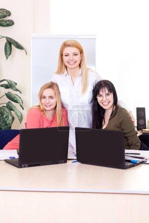 Foto de El equipo de negocios en el espacio de trabajo busca en las computadoras. Profesor en la sala de clases enseña mujeres de mediana edad . - Imagen libre de derechos