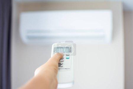 Photo pour Main humaine appuyez sur la télécommande du climatiseur par temps chaud. Le sujet est flou . - image libre de droit