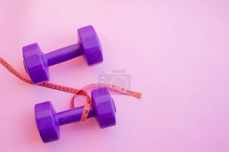 Fitness equipment dumbbells on color background. F...