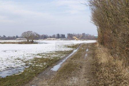 Sale route de campagne à côté du champ neigeux