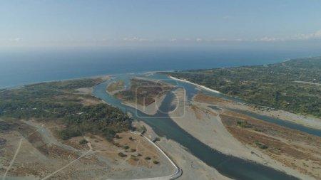 Photo pour Vue aérienne de rver coulant dans la mer aux Philippines, Luçon. paysage ropique avec côte sablonneuse et rivière parmi les champs agricoles coulant dans l'océan bleu - image libre de droit