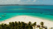 Tropical Daco Island with a sandy beach and tourists.