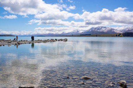 COLLINGWOOD, NEW ZEALAND - OCTOBER 5 2018; Family four Asian tourists photographing scenery and enjoying waters edge and great views.