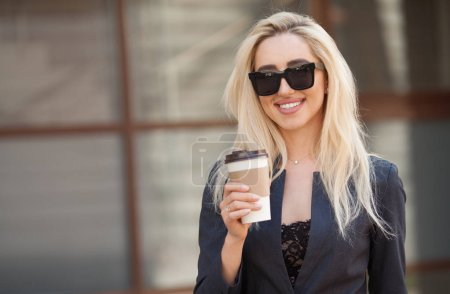 Photo for Cheerful female manager getting to work by foot drinking morning coffee to go while walking street, successful businesswoman in elegant wear enjoying sunny weather - Royalty Free Image
