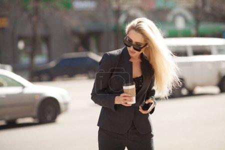 Photo pour Gai manager féminin arriver au travail à pied, boire du café du matin pour aller tout en marche femme d'affaires de la rue, avec succès une usure élégant bénéficiant d'un temps ensoleillé - image libre de droit