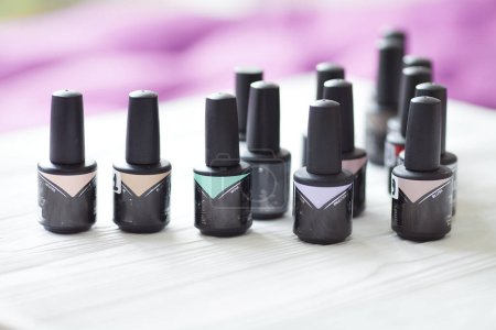 Photo for Group of nail polishes of different colors on blurred background - Royalty Free Image