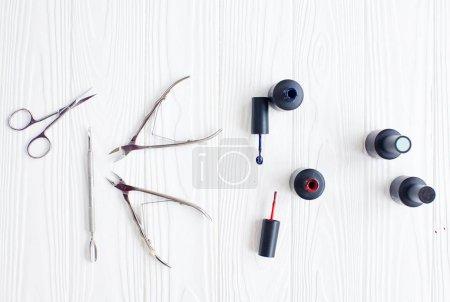 Photo pour Tube ouvert de vernis à ongles bleu et rouge et une brosse sur un fond blanc - image libre de droit
