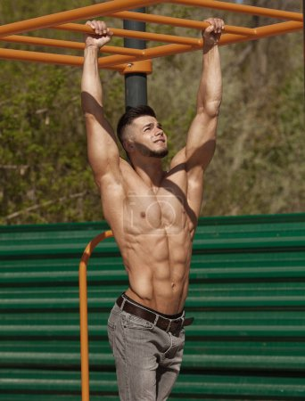 Photo for Muscular man working out doing stomach exercises outdoor. Strong male naked torso abs - Royalty Free Image