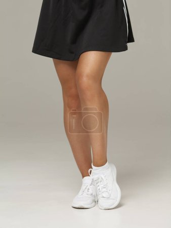 Photo for Close-up of beautiful female legs in sport wear over gray background - Royalty Free Image