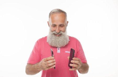 Photo pour Discussions animées. Vieil homme aux cheveux blancs ayant une conversation au téléphone et gesticulant émotionnellement tout en posant isolé sur un fond blanc - image libre de droit