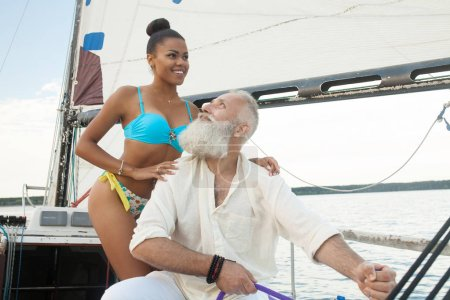 Happy elderly senior with african woman travel on yacht.