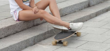 Photo for Casual blond female in denim shorts posing on stairs with longboard. - Royalty Free Image