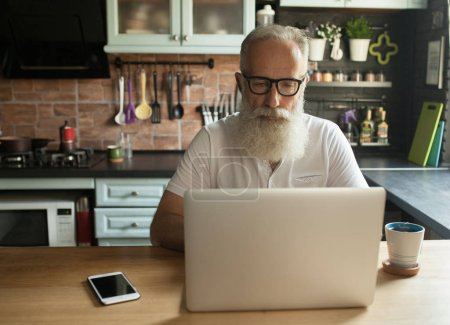 Photo for Mature bearded man with laptop and eyeglasses - Royalty Free Image